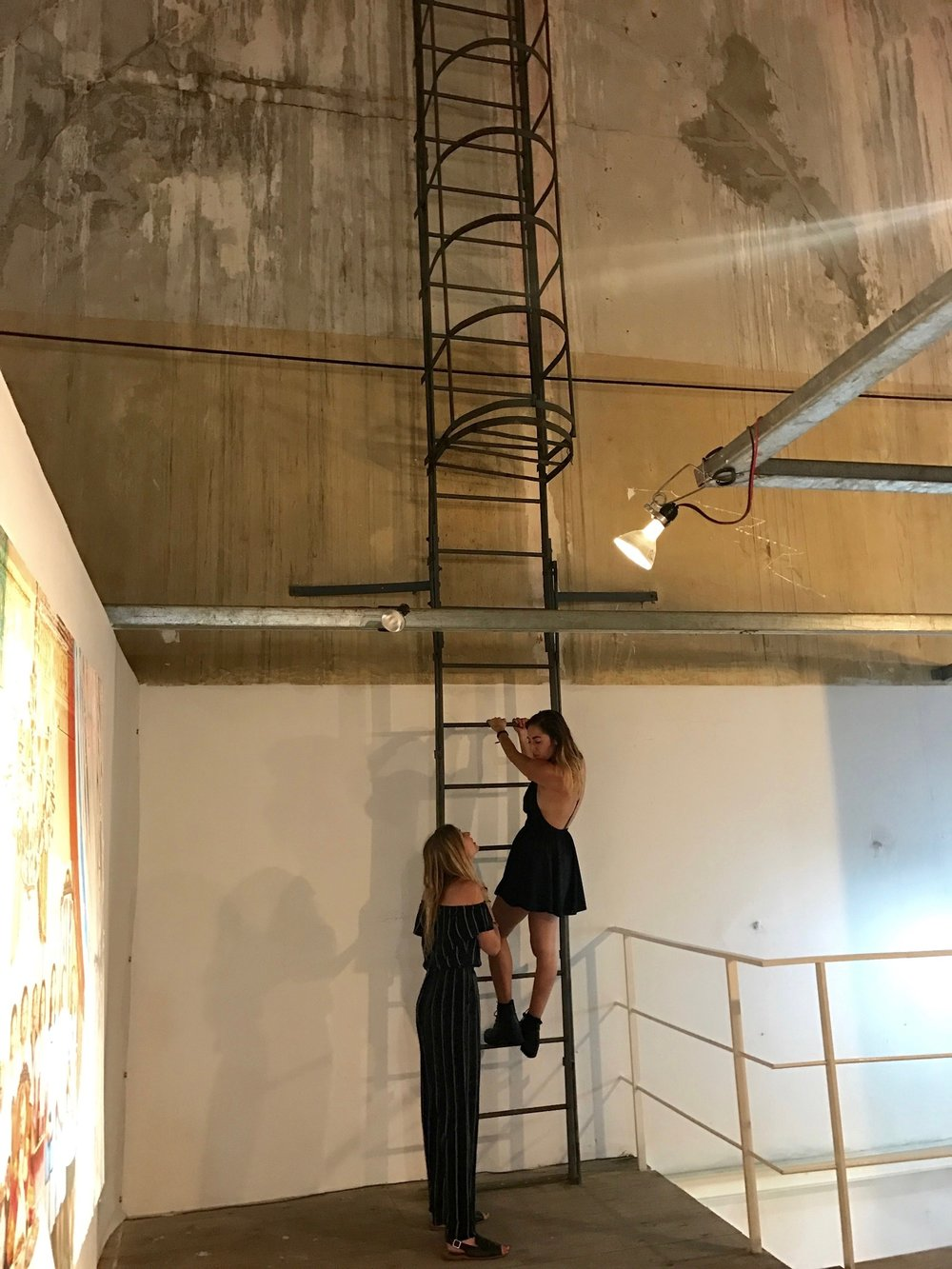 Megan talking me down from climbing the ladder at Fabrica de Arte Cubano.