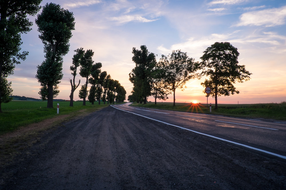 The road in this photo of the Polish countryside is working as a leading line by drawing your eye into the image and towards the setting sun.