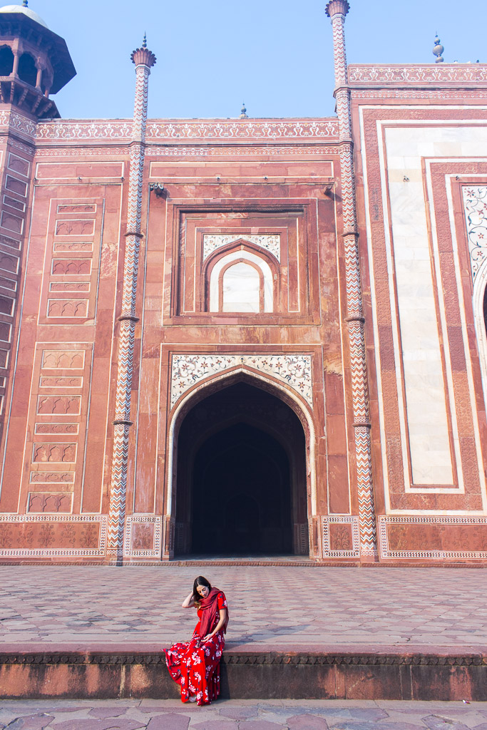 Sitting in front of the red sandstone wall on the left side of the Taj Mahal.