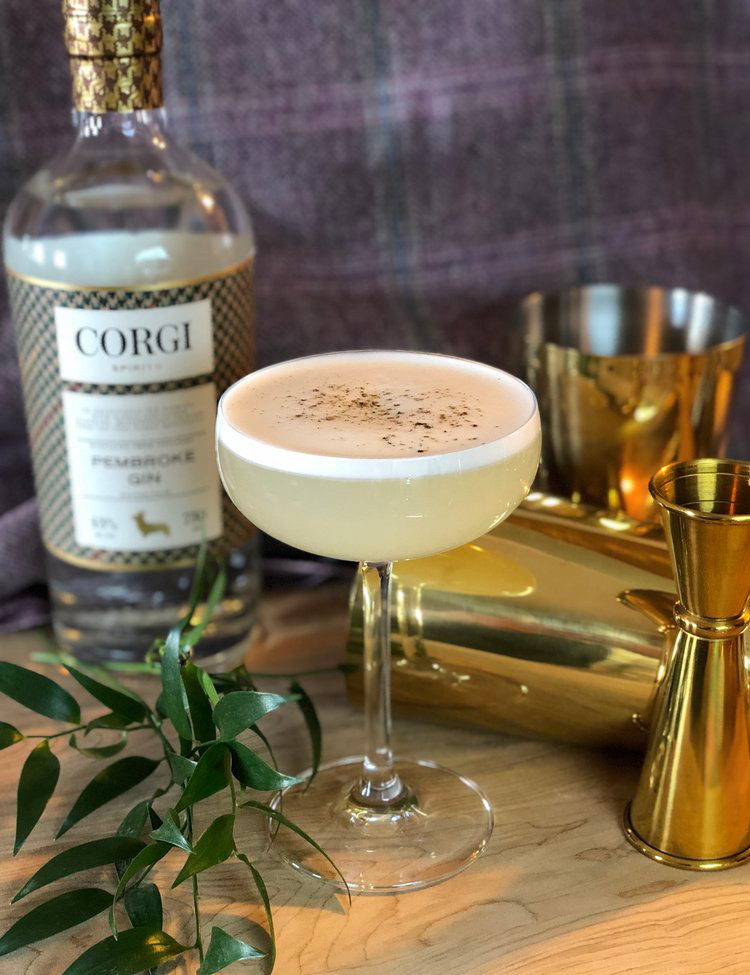 PEP IN YOUR STEP   2oz Corgi Spirits Pembroke Gin  0.5oz fresh lemon juice  0.75oz pink peppercorn syrup (see below)  1 egg white  Cracked black pepper for garnish    Add all ingredients to shaker and shake vigorously. Open shaker, add ice, and shake again until well chilled. Strain into a chilled cocktail glass and garnish with cracked black pepper on top.  To make pink peppercorn syrup, combine 1 cup water with 1 cup sugar and 4 tbs crushed pink peppercorns in a saucepan and bring to a boil. Remove from heat and allow to steep until cool. Strain and reserve syrup.