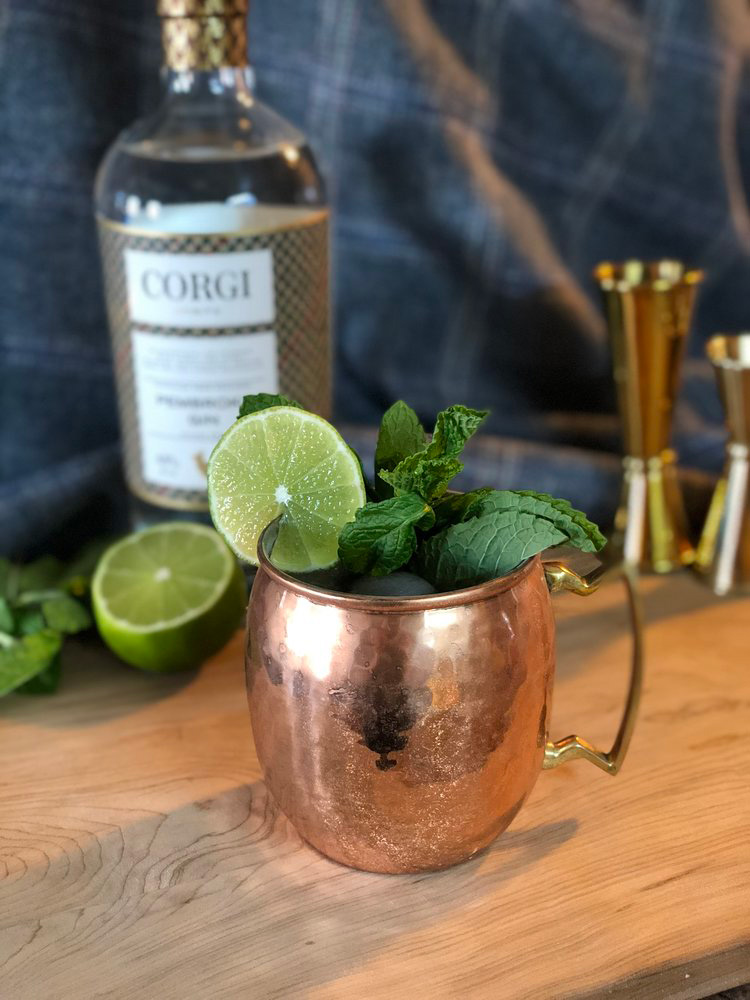 GIN-GIN MULE   1.5oz Corgi Spirits Pembroke Gin  0.75oz fresh lime juice  1oz simple syrup (1 part sugar : 1 part water)  8 mint leaves  Ginger beer (Fever Tree preferred)  Lime wheel and mint sprig for garnish    In a cocktail shaker, muddle mint leaves, add ice, gin, lime juice, and syrup, and shake vigorously. Strain into a copper mug over fresh ice, top with ginger beer,and garnish with lime wheel and mint sprig.  Recipe from Audrey Saunders