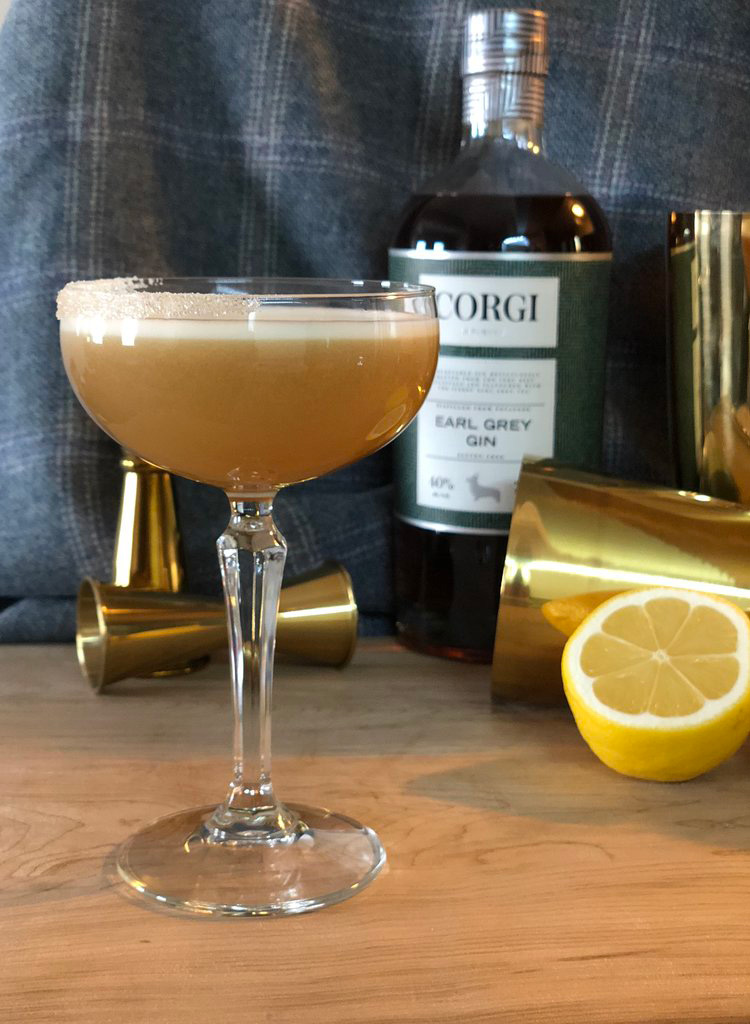 EARLTEANI   1.5oz Corgi Spirits Earl Grey Gin  0.75oz lemon juice  1oz simple syrup (2 honey : 1 water)  1 egg white  Sugar rim and lemon twist for garnish    Fill a shaker with ice, add all ingredients, and shake vigorously. Pour into a chilled cocktail glass half rimmed with sugar. Add lemon twist as garnish.  Recipe from Audrey Saunders