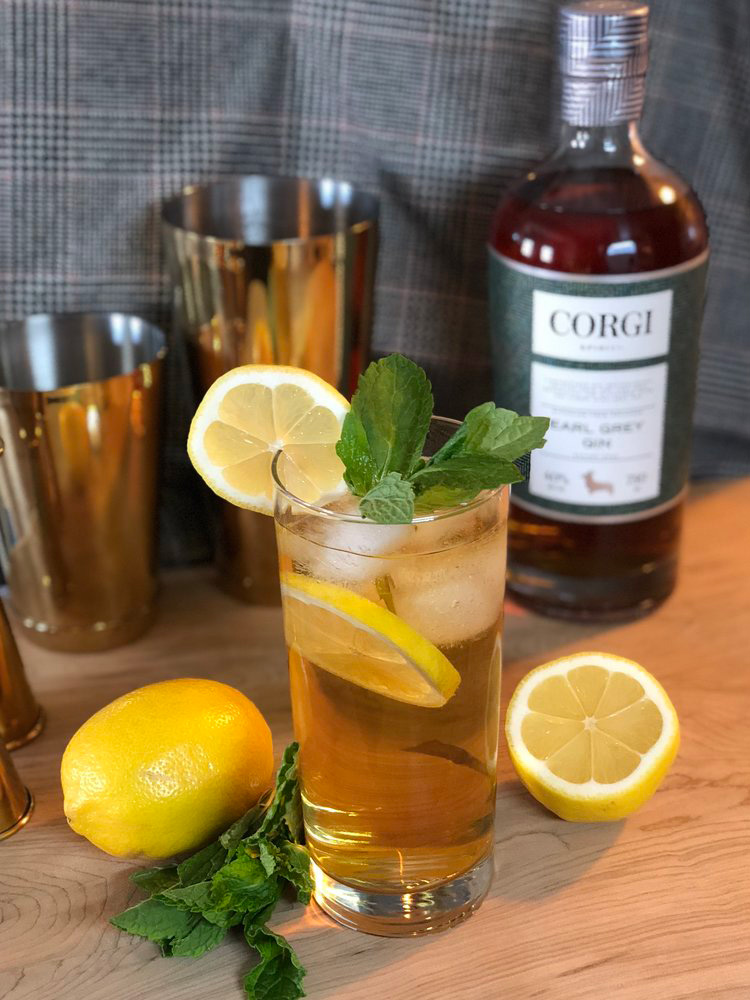 TEA & MINT COLLINS   1.5oz Corgi Spirits Earl Grey Gin  0.75oz fresh lemon juice  0.75oz simple syrup (1 part sugar : 1 part water)  5-6 mint leaves  Club soda  Lemon wheel and mint sprig for garnish     Fill a shaker with ice, add gin, lemon juice, mint, and syrup, and shake vigorously. Strain into a Collins glass over fresh ice and top with club soda. Garnish with lemon wheel and mint sprig.