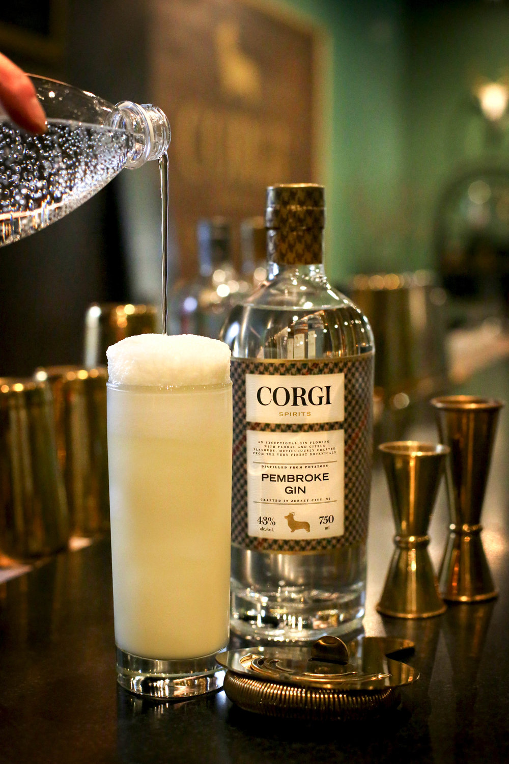 RAMOS GIN FIZZ   2 oz Corgi Spirits Pembroke  1 dash orange blossom water  0.5 oz 1/2 & 1/2  0.5 oz lemon juice  0.5 oz lime juice  0.5 oz simple syrup  1 egg white  1oz seltzer water    In a shaker combine all ingredients excluding the seltzer. Vigorously dry shake (no ice) for 30 seconds. Add ice and vigorously shake for 30 more seconds. Strain cocktail into glass and slowly pour the seltzer water into the mixing glass to release the remaining froth. Gently ease the seltzer water/froth mixture onto the top of the drink and serve.