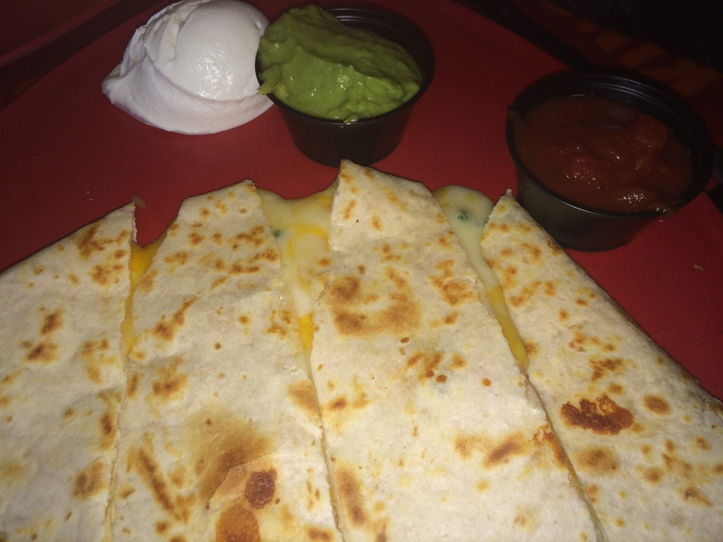The cheese quesadilla with salsa, sour cream, and guacamole