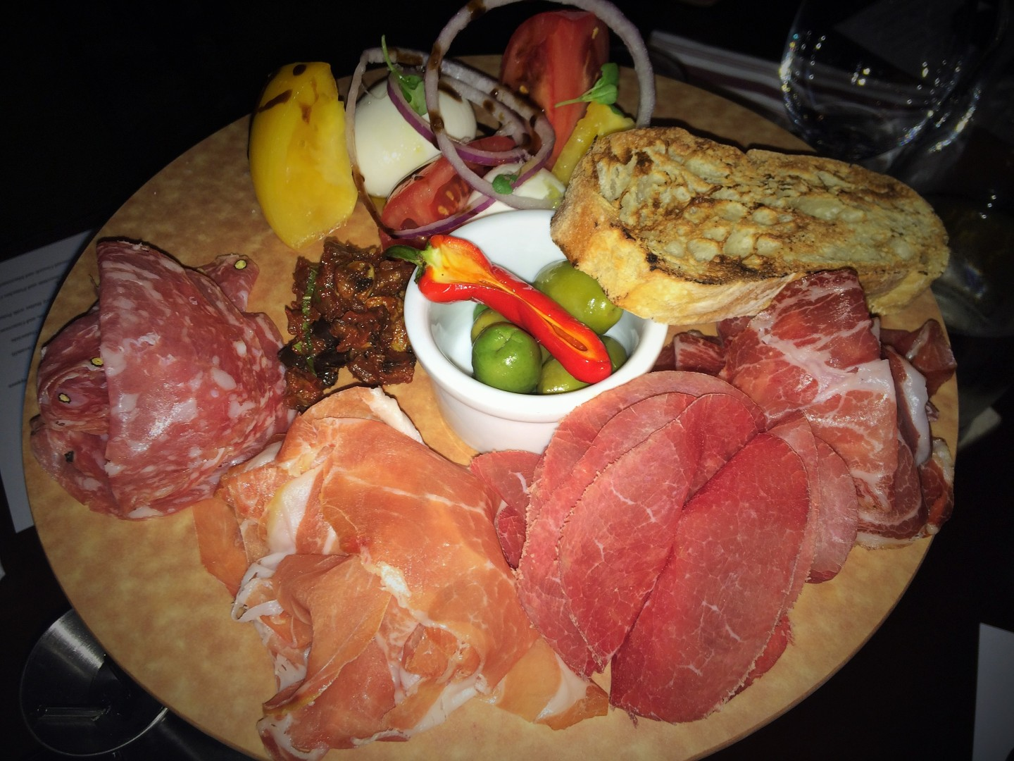 An antipasti platter with cured Italian meats, house-pickled peppers, olives, freshly made mozzarella, heirloom tomatoes, and caponata.