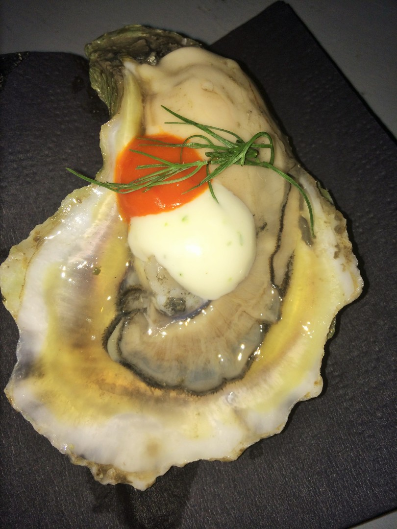 A raw oyster with some sort of cream and hot sauce