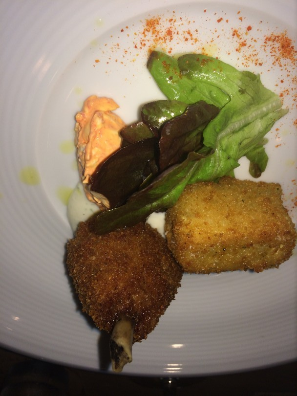Chicken wing with fried green tomato salad, buttermilk nage, and onion scapes