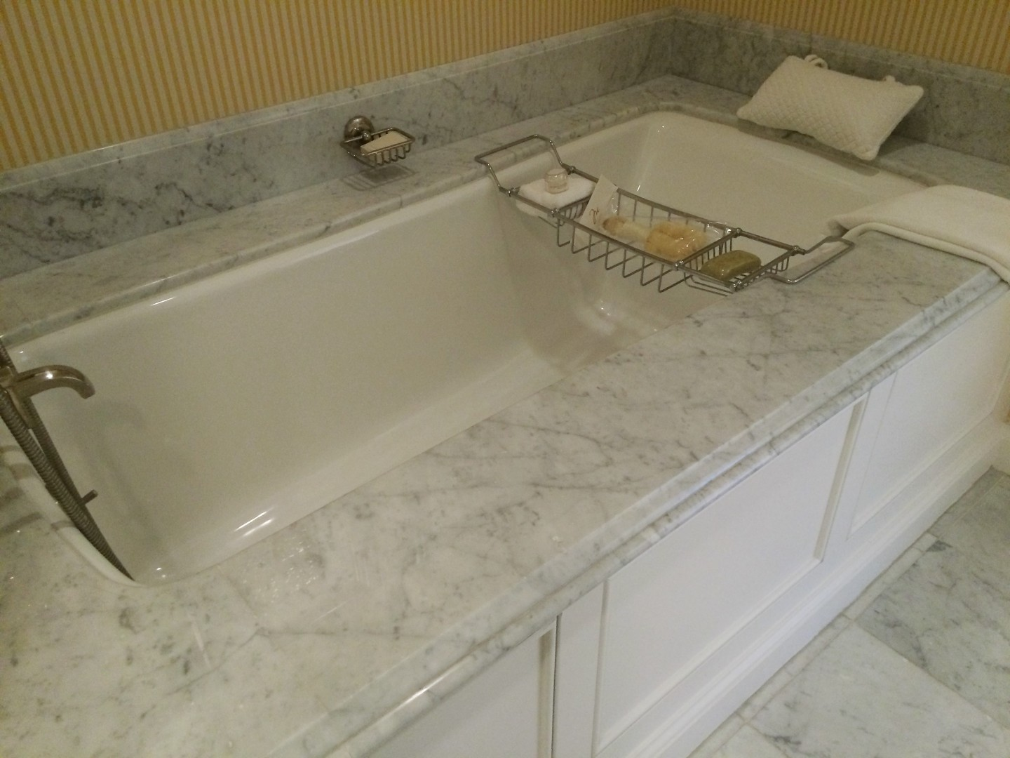 Look closely, and you'll see that the marble bathtub has a rack for keeping doodads, and a pillow (a pillow!).