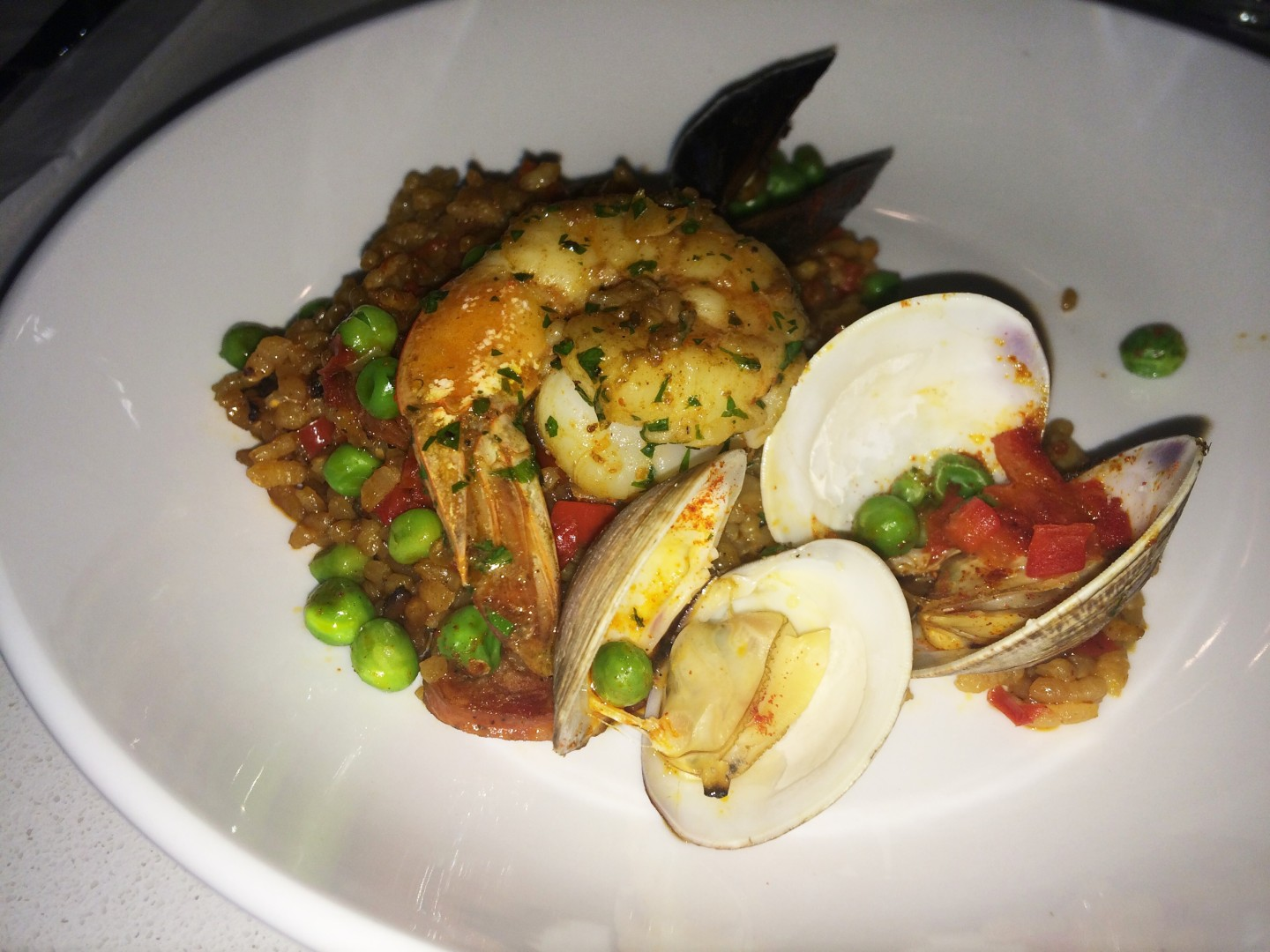 Seafood paella with clams, shrimp, mussels, chorizo, peas, pimienton, saffron, and lemon