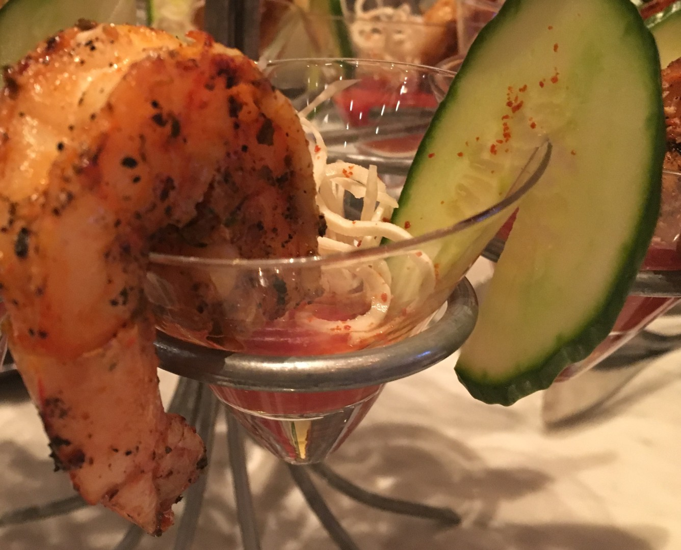 Grilled, herbed shrimp cocktail with bloody mary cocktail sauce, shaved horseradish, and sliced cucumbers