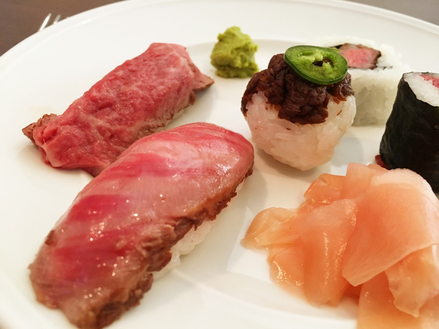 Matsusaka beef sushi platter, clockwise from the shiny on the front left: New York Strip tataki nigiri, flash-seared filet sushi roll, raw filet maki roll, spicy tuna roll, round beef cooked in mirin and soy and topped with jalapeno