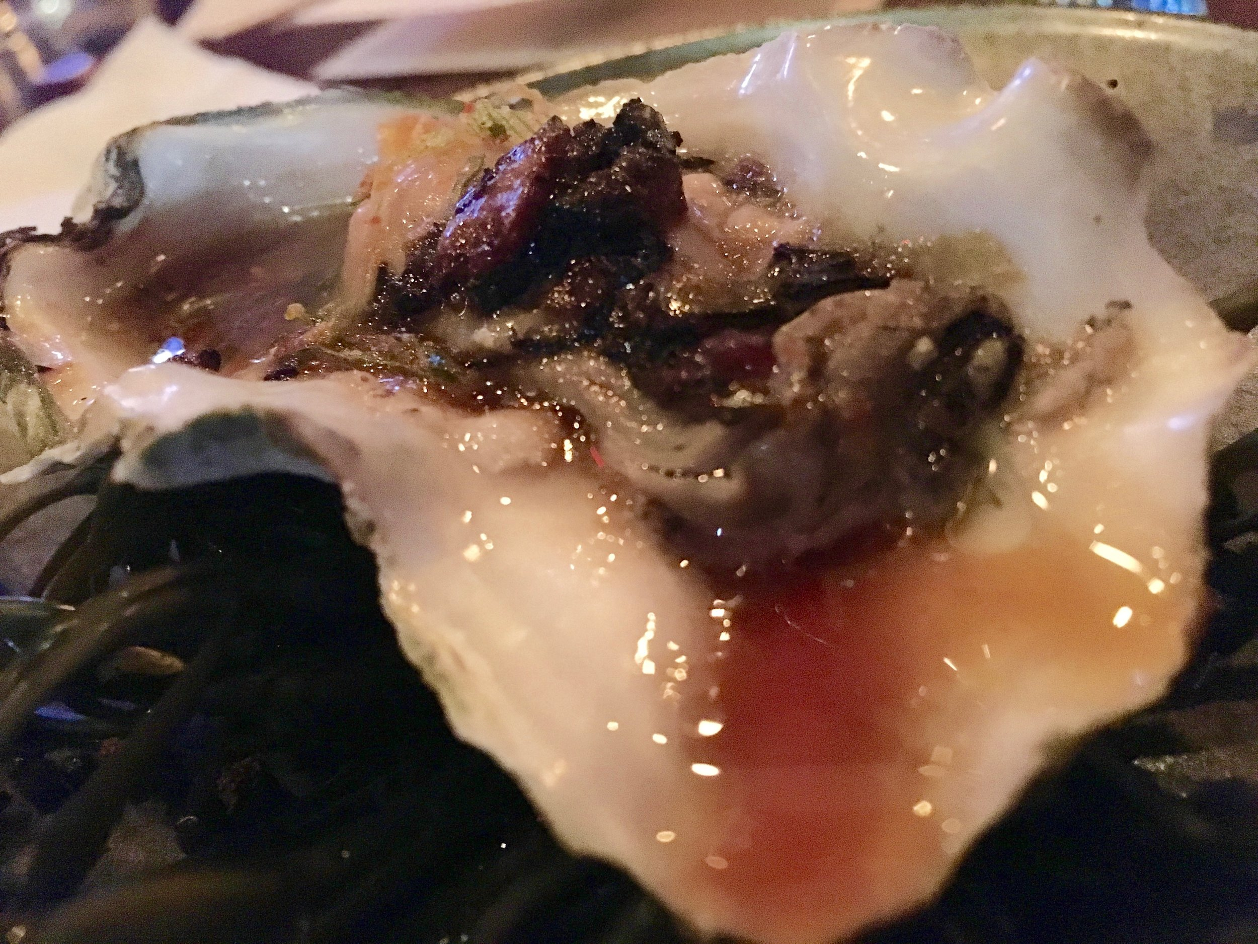 Grilled oyster with black bean pesto, fried scallions and ginger-soy sauce at the omakase dinner at Seito Sushi