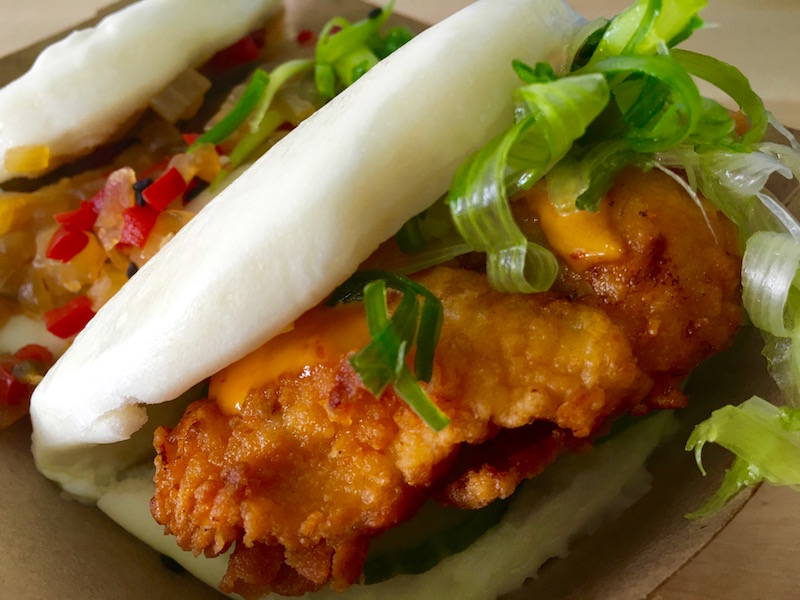 The front bao from King Bao restaurant is the Kickin Chicken, filled with kimchi-fried chicken, cucumber, sriracha aioli and scallions. Behind it is the meeker Veganville, a crispy tofu bao wit a shallot-ginger-pepper relish.