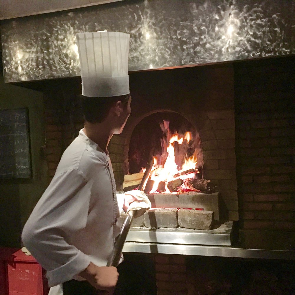 A Duck de Chine chef placing ducks in the fire, which help the pre-seasoned poultry get a lusciously thin and crispy skin