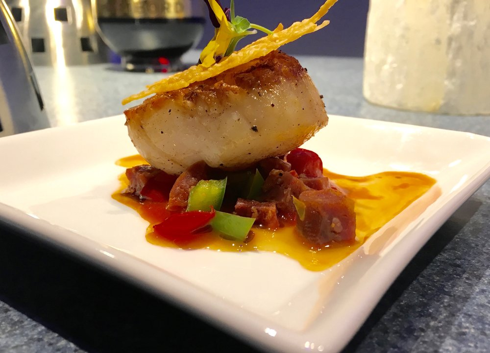 This scallop from The Artist's Table is pan-seared and plated with chorizo, roasted red pepper coulis and a Parmesan crisp.