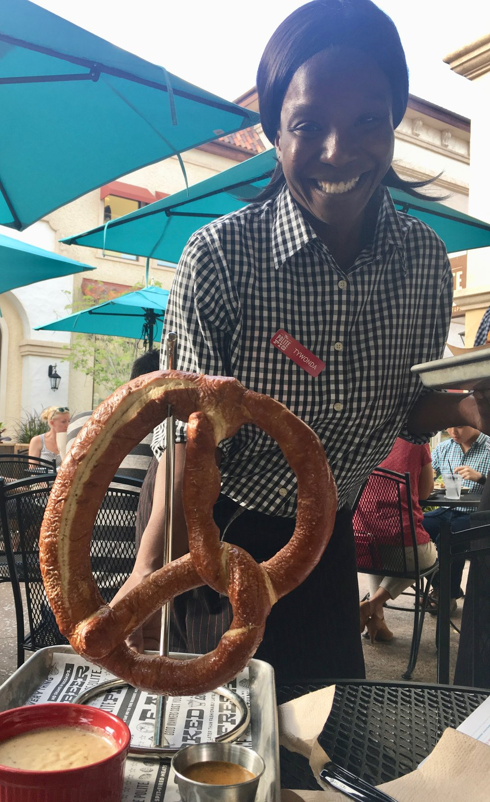 Once he saw this pretzel delivered to another table, The Hub had to try it. What a great presentation. Here, a server agreed to pose with the oversized twisted, salted bread. The Hop Salt Pretzel is served on that hanging gadget with a crock of beer cheese fondue and a cup of IPA mustard.