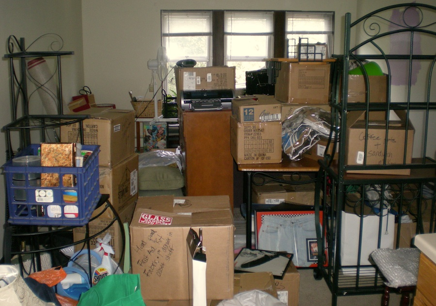 A very cluttered room with boxes and furniture everywhere