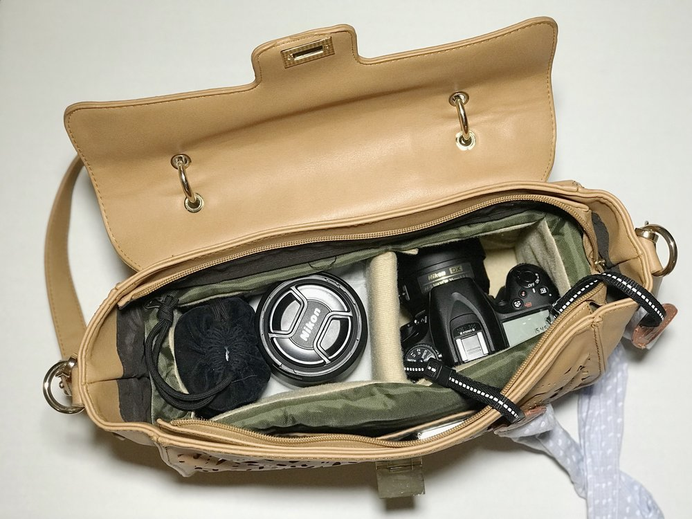 This is what the inside looks, most of the time. The 35mm is on my camera, and I carry the 50mm and the 85mm right underneath it. The flash I keep in a velvet bag, only because I hardly use it and don't need easy access to it. Most of the other things are around there, somewhere!