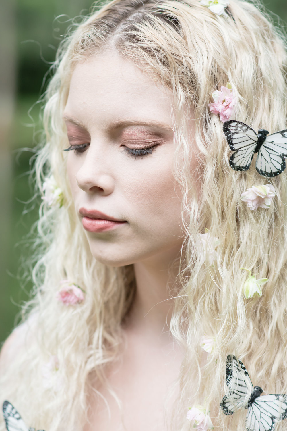 close of bridal makeup with florals and butterflies on hair