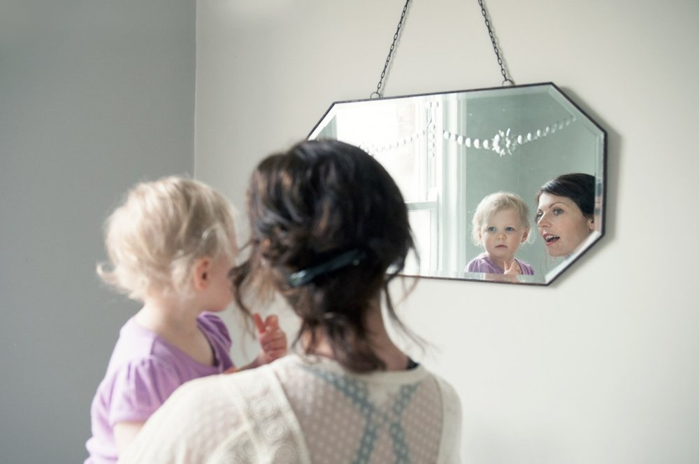 Reflection - Frame position : Near the subjectType of frame : MirrorNotes : The key to this is that the mum and daughter are only in focus in the mirror. If the back of their heads were in focus, but the reflections blurry, it wouldn't work at all.