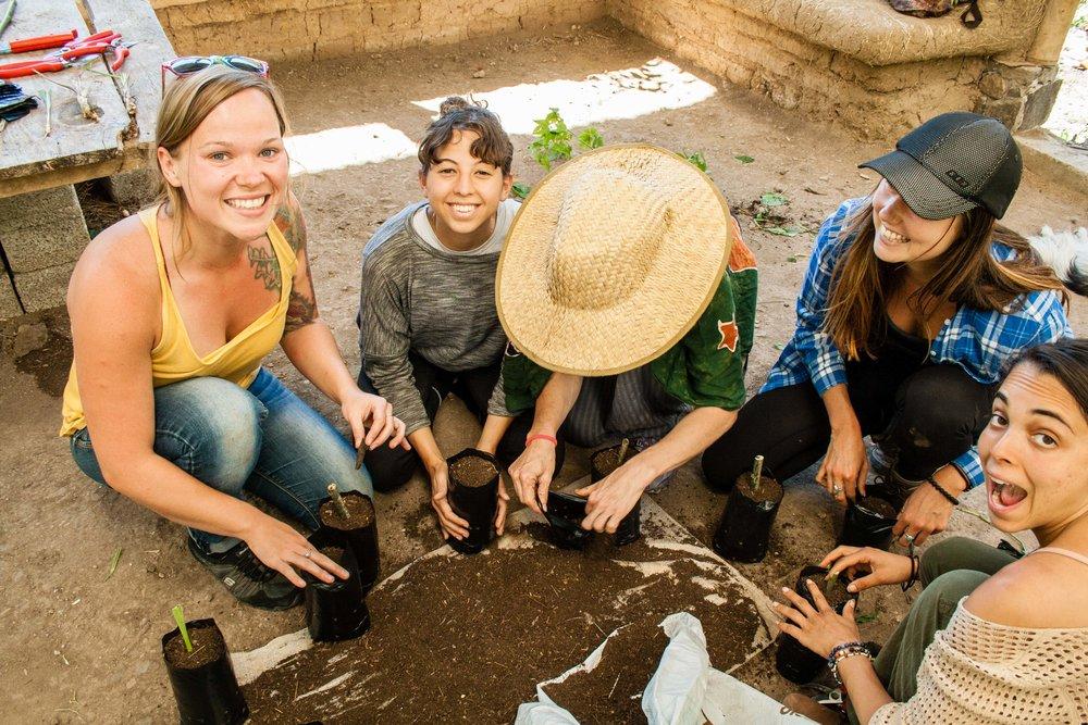 Happy participants smile at camera while preparing Permaculture garden at Atitlan Organics, permaculture design course, Lake Atitlan, Guatemala