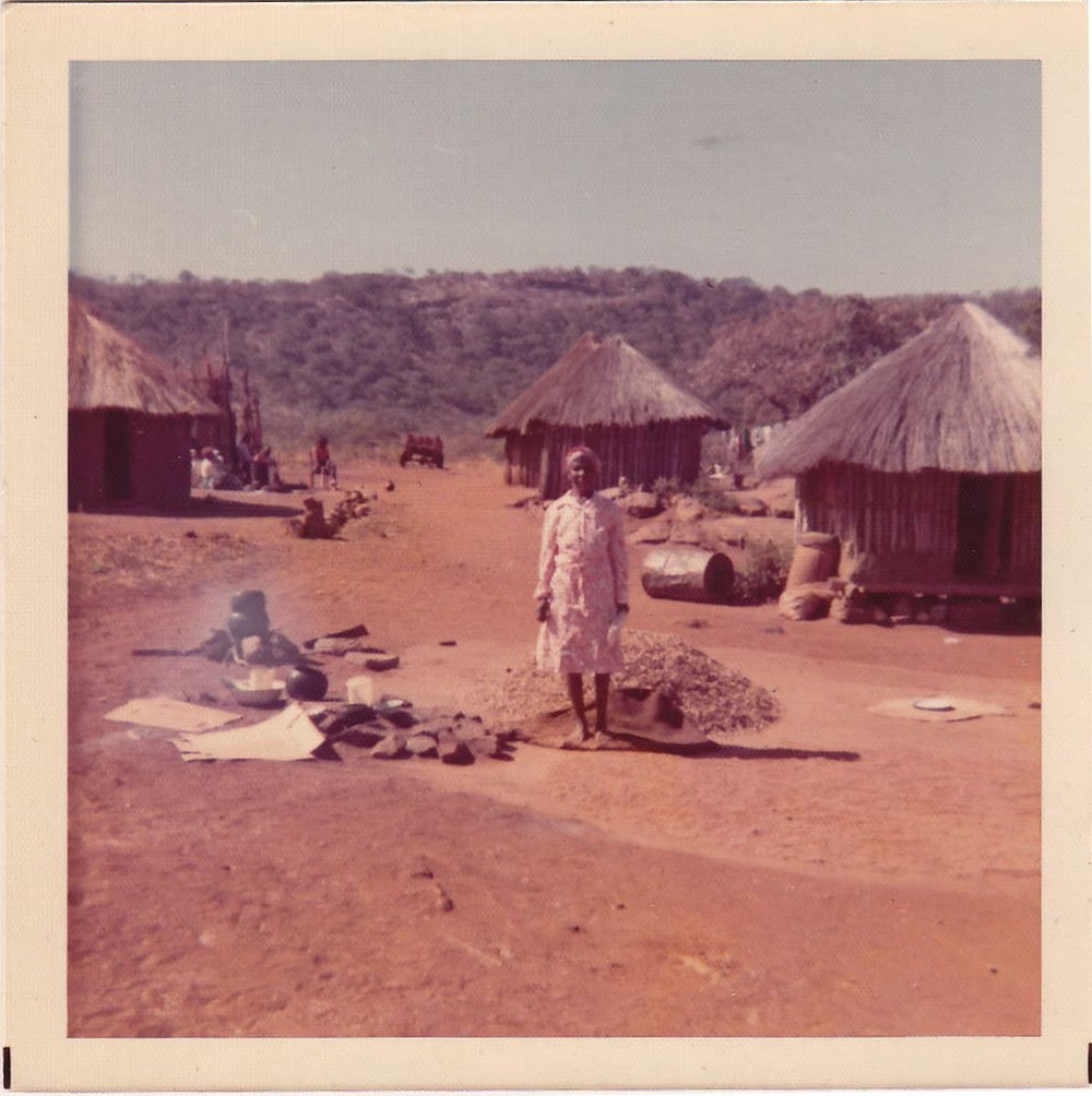 Phillip's Amai(mother) preparing the lunchtime meal.The hut to the right is the hosi(grain silo), while the hut on the left is the kicheni(kitchen).
