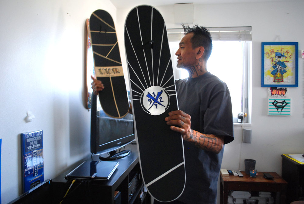 Michael shows off his skateboards bearing the logo of his future art studio.