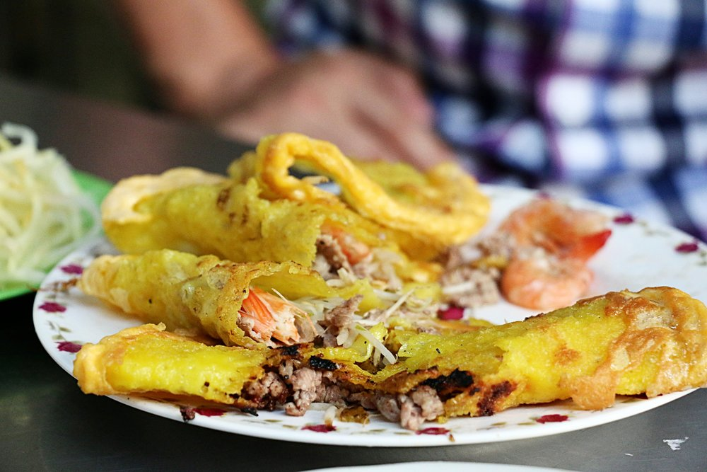 These turmeric crepes are thin, slightly chewy and crispy. The texture is phenomenal, especially when you bite into them and get a mouthful of the juicy fresh water prawns, pork, and bean sprouts. All these cooked inside the crepe makes it juicy, moist and crisp at the same time. I could eat these just by itself all day long.