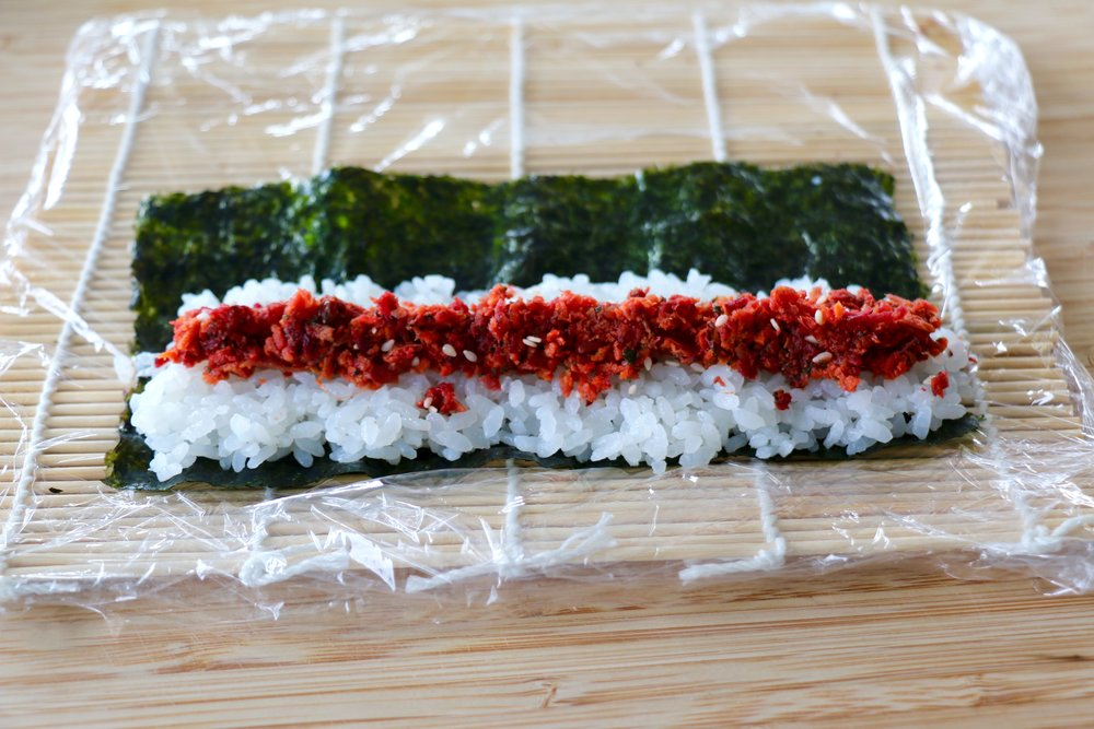 Thin layer of rice on a quarter of the nori sheet with some pickled Juicero beet pulp