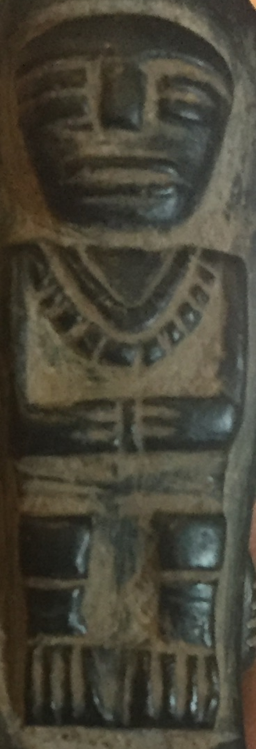 The triangle above this figures necklace identifies it as a female adult.