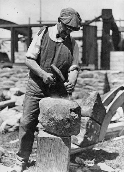 A Victorian scelper chipping a stone into form.