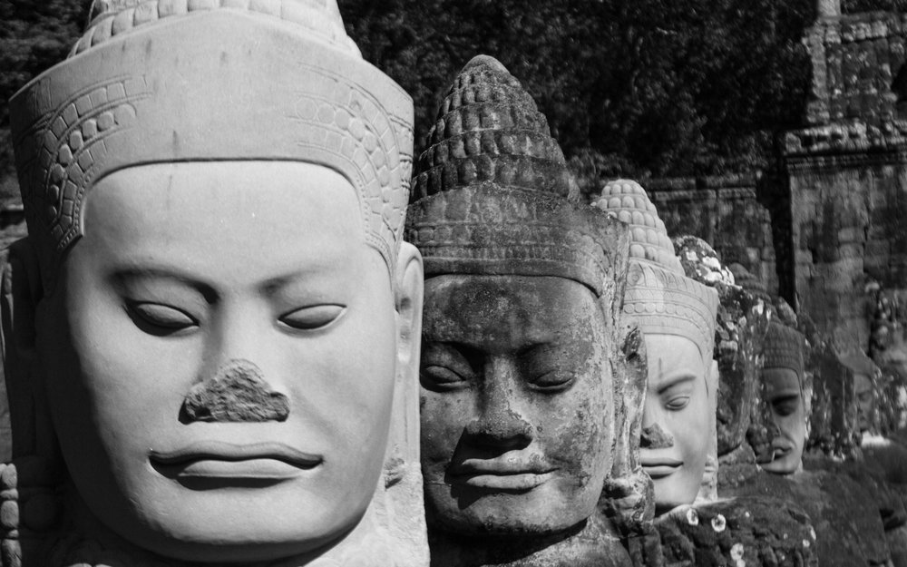 Buddha busts lining the south entrance to the Angkor Wat complex.  ©ashleycowie.com