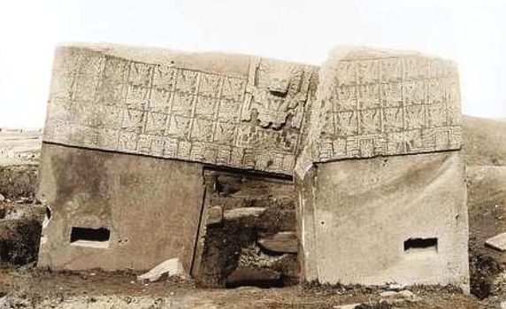 Figure 5: 1903 photograph of Tiwanaku's Gateway of the Sun. Carved with an image of the creator god Viracocha holding two lightening bolts. Where this monument stands today is not its original position.  Public License .