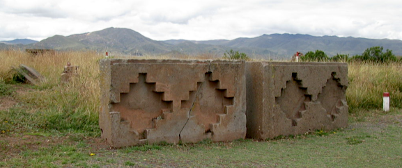 Figure 7. These two 20 ton blocks lie to the north of the Akapana pyramid and display a stepped symbol reflecting the shape of the distant mountains.  Public License.