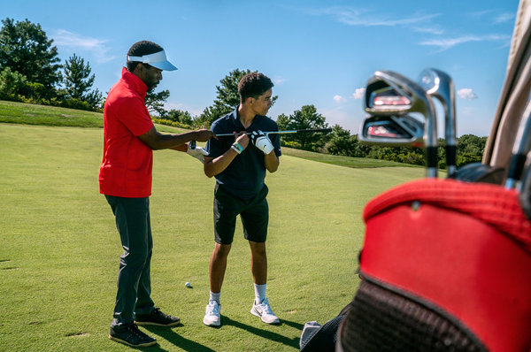 Farrell Evans, left, a co-creator of the Bridge Golf Foundation, works with Juan Cortorreal, 15.  Image:  JOHNNY MILANO FOR THE NEW YORK TIMES