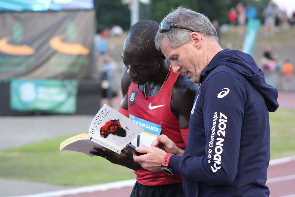 """Lomong signs a copy of his book, """"Running for My Life"""" for a fan in Ireland."""