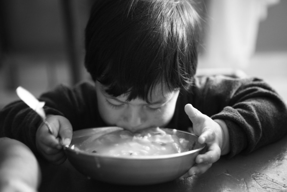 Orphan eating soup