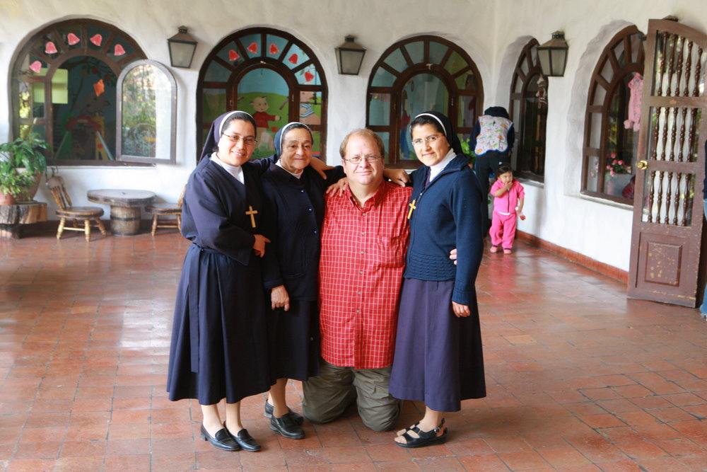 Rex on his knees pictured with orphanage nuns (not Sor Mariana)