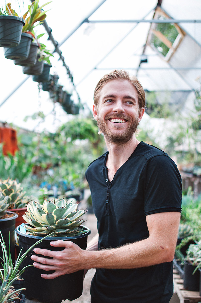 """Corey lived in Hawaii for six years, and volunteered at the Lyon Arboretum, which is the only arboretum in a rainforest in the U.S. He hasn't had a car in ten years. He likes being a minimalist and doesn't want to drive in Austin traffic. His photo was taken at East Austin Succulents.   """"The train bypasses all the traffic. It's a known quantity. It's a 13 minute trip no matter what, which is really nice as opposed to 30 or an hour. I like the ability to do stuff on the train or bus, like read or work online or do something productive as opposed to just sitting behind a wheel."""""""