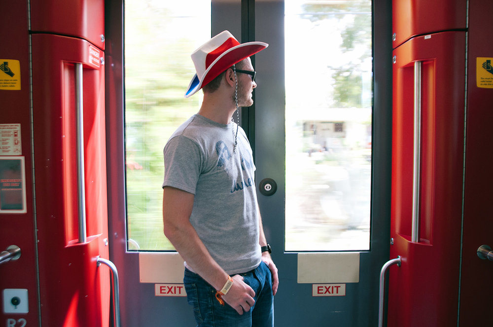 "Tom is a software engineer and received his hat as a going away gift when he moved to Austin. He was taking the train from where he lives in North Austin.   ""I'm taking the train into the Zilker Park area for Austin City Limits. I haven't been to the festival before and I'm not sure how parking is going to be. And they have the train extended schedule which helps out alot with the festival."""