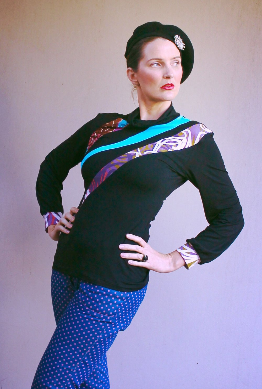 A black jersey knit Skivvy blouse with contrasting colours and prints of Aqua, purple, white and pink.