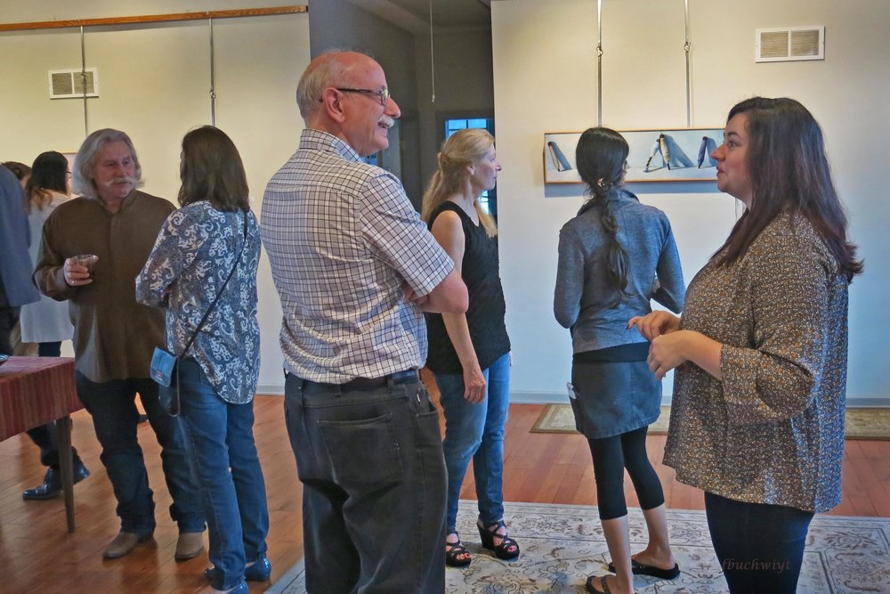 Claira talking to LHU Art professor, Raymond Heffner, while people enjoy the exhibit.