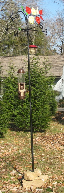 A bird feeder/weather vane stand