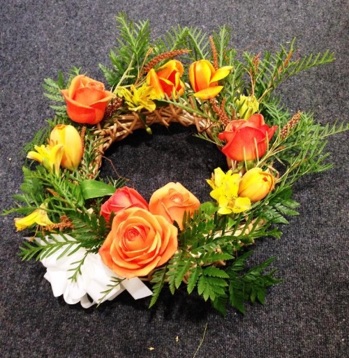 A stylish funeral wreath designed with the families favourite colours and greenery from there trees.