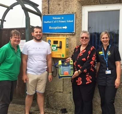 Shalfleet Primary School proudly shows that their IW NHS Trust defibrillator is now available 24/7 thanks to The Island Savoyards.     From left to right; Paula Blackley, Andrew Woodford (Island Savoyards), Sue Shynn and Louise Walker