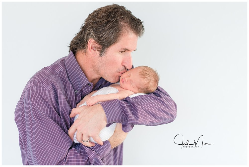 Baby Amelia being held by her proud daddy during the newborn session at the Florez family home in Scottsdale, Arizona.