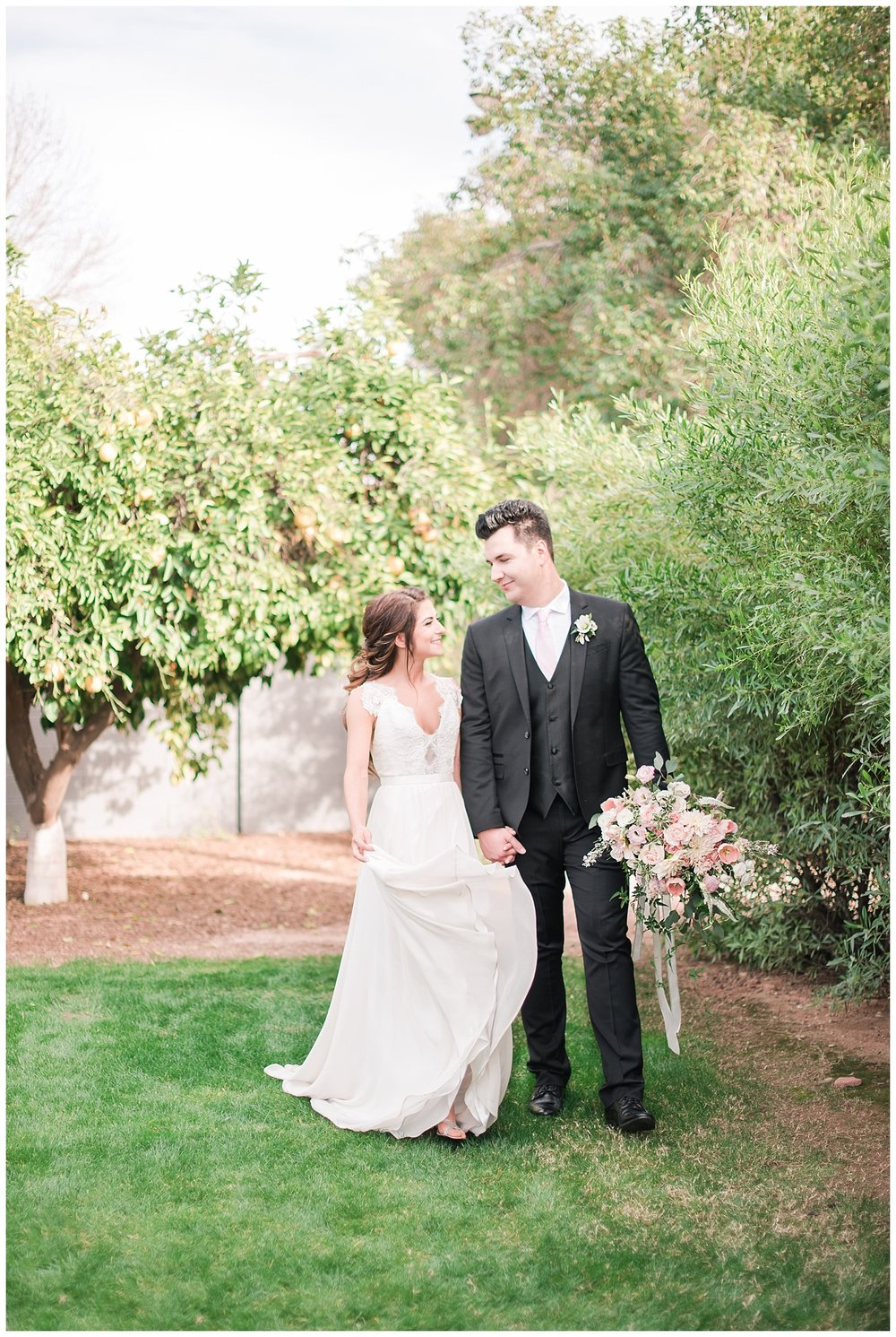 Beautiful bride Jessica wearing dress provided by Bella Lily Bridal in Phoenix and dashing groom holding bouquet made with love by Garden Gate Flowers, photographed at Gather Estate in Mesa, Arizona.