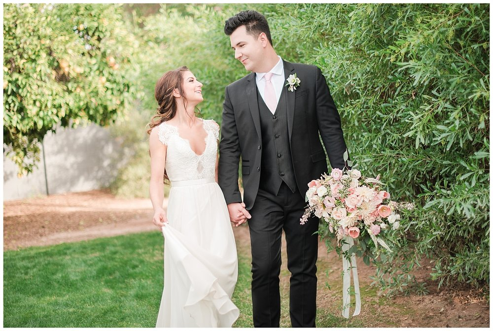Beautiful bride Jessica wearing dress provided by Bella Lily Bridal in Phoenix and dashing groom Slaven holding bouquet made with love by Garden Gate Flowers, photographed at Gather Estate in Mesa, Arizona.