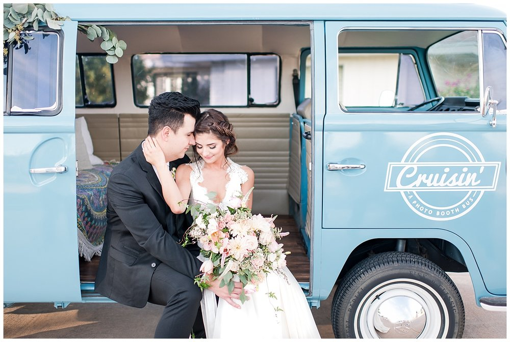 Bride Jessica wearing dress provided by Bella Lily Bridal in Phoenix and nuzzling with groom Slaven inside Cruisin -  a Photo Booth Bus, photographed at Gather Estate in Mesa, Arizona.